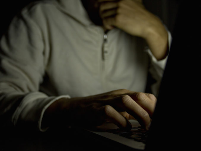 Concept of internet addiction, man on laptop at night